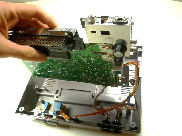 Pull the motherboard assembly straight up and out of the plastic case with your hands.