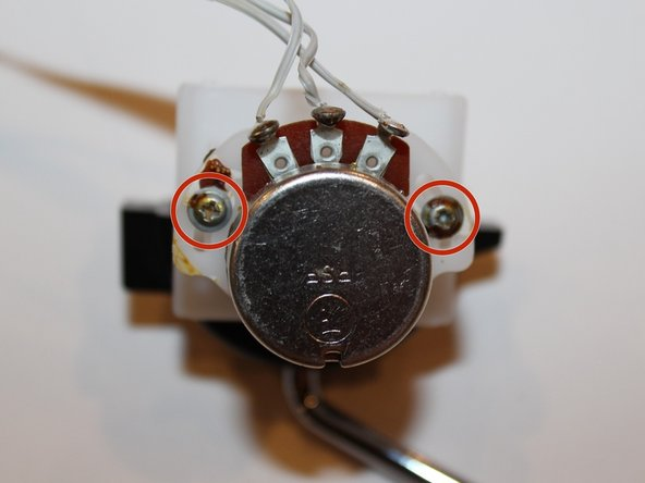 Remove the two screws with a philips head screwdriver. Each screw is 0.8 cm.