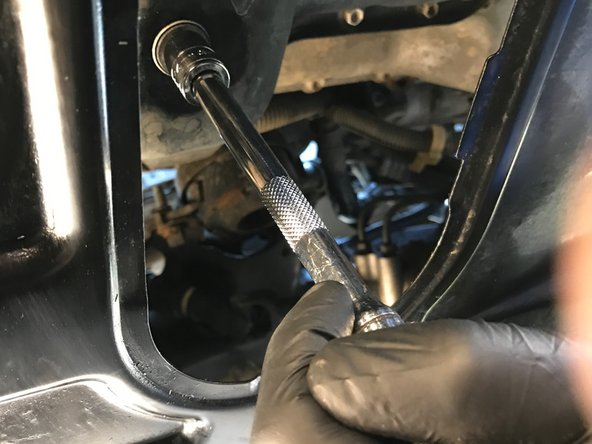 Image 1/3: Use a 14 mm box end wrench or socket wrench to loosen the oil drain plug by turning it counter-clockwise until you can turn it by hand.