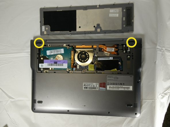 Remove the rubber pads near where the hard drive cover was using a sharp pair of tweezers.