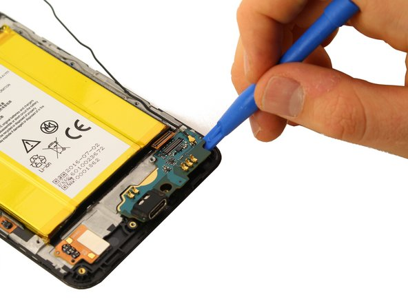 Wedge the plastic opening tool under the charging port board at the bottom of the phone.