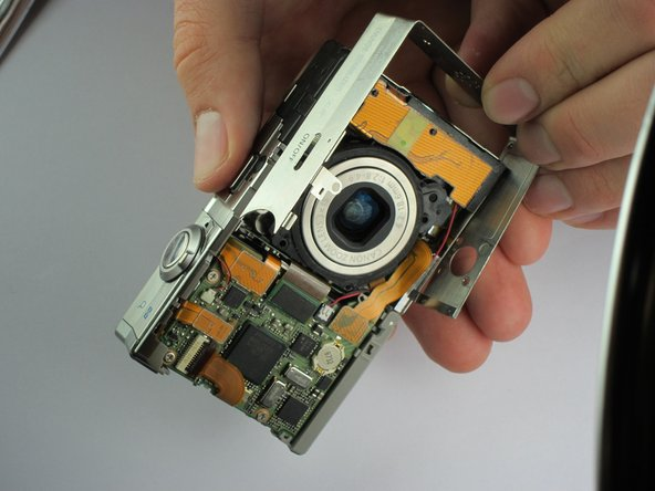 Image 1/3: Starting with the side plate, line it up and snap it back into place on the camera.