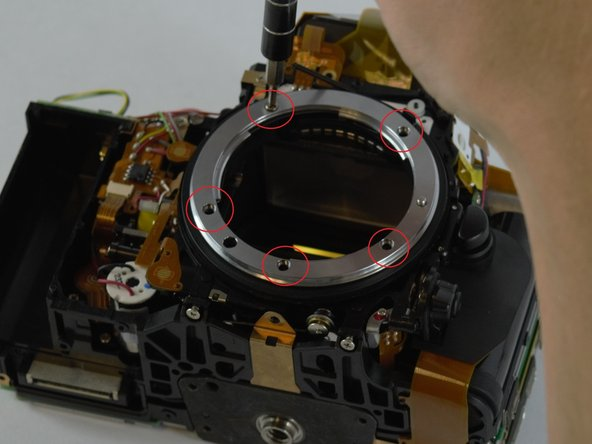 Begin by removing the silver ring around the lens socket by unscrewing the five screws supporting it.
