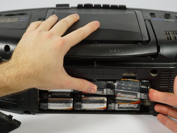 Push against the positive end of each battery. Once it is loose, lift the battery out. Repeat for all six batteries.