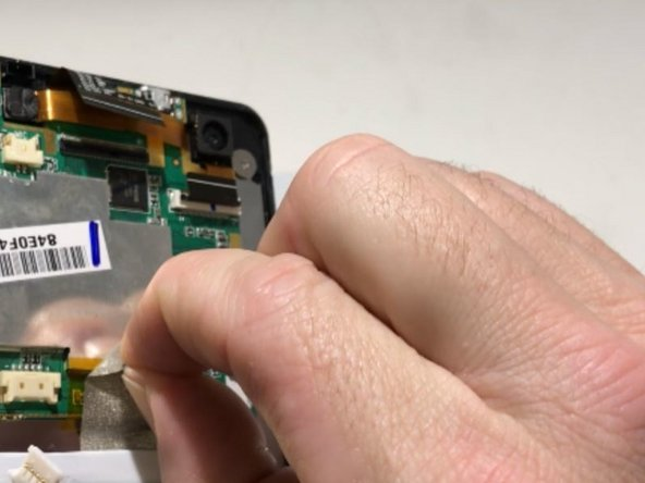 Peel back the metallic tape connecting the motherboard to the tablet body with your fingers.