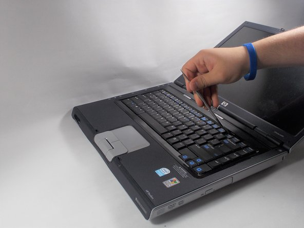 Using a metal spudger, pry up on the plastic piece above the keyboard containing the power button.