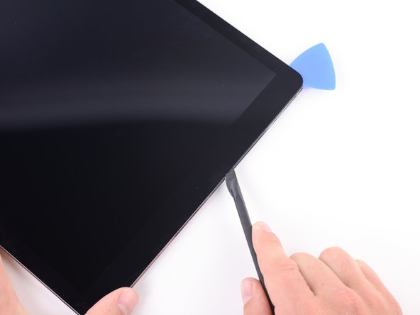 Image 3/3: Slide the blade along the top edge of the iPad, stopping before reaching the front-facing camera.
