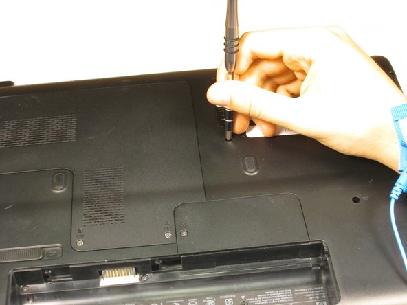 Remove the 6mm screw above the laptop stickers using a Phillips #0 screwdriver.
