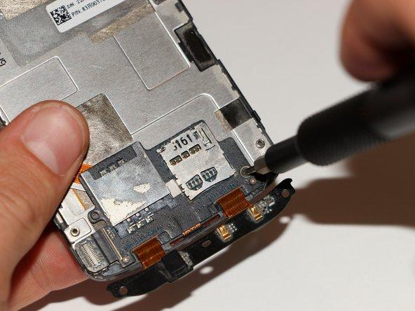 Nimm jetzt die Displayeinheit zur Hand und entferne die Philips-Ph00-Schraube am unteren Rand mit einem Schraubendreher.