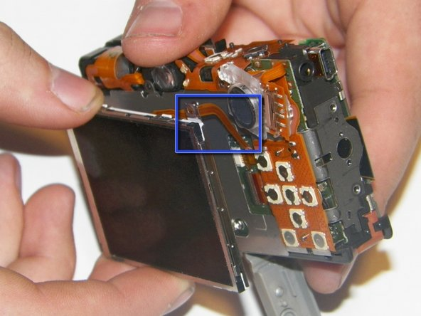 Image 2/3: Gently pull the wide ribbon (shown in an earlier step) cable from the front of the camera to the back using tweezers.