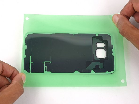 Grasp the adhesive from both sides and align the tape over the rear glass.
