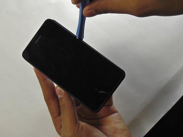 Abre la tapa posterior del teléfono con la herramienta de apertura de plástico.