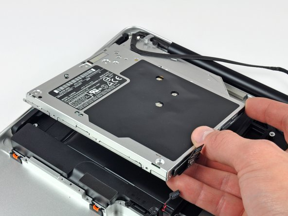 Lift the optical drive from its left edge and pull it out of the computer.