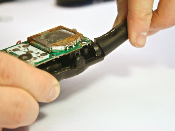 Image 1/3: To do this, grip the back faceplate in one hand and the antenna in the other. Pull and twist the antenna away from the back faceplate. The circuit board should be removed with the antenna, as they are attached.