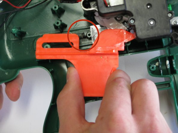 Lift the plastic trigger away from the gun  along with the attached spring.