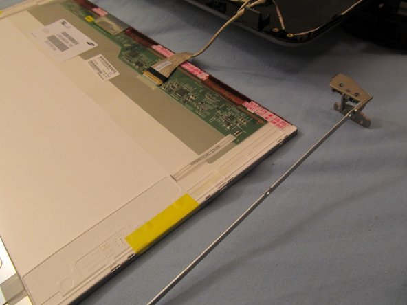 Image 1/1: Once the LCD is on it's face (and the cables are still intact) remove the 6 screws holding the metal LCD holders in place. There are 3 screws on each side.
