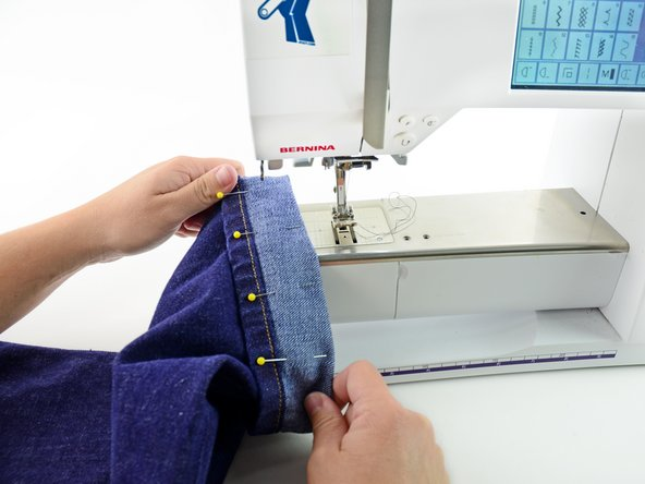 Set up your sewing machine with thread that matches your jeans and a heavy-duty/denim needle.