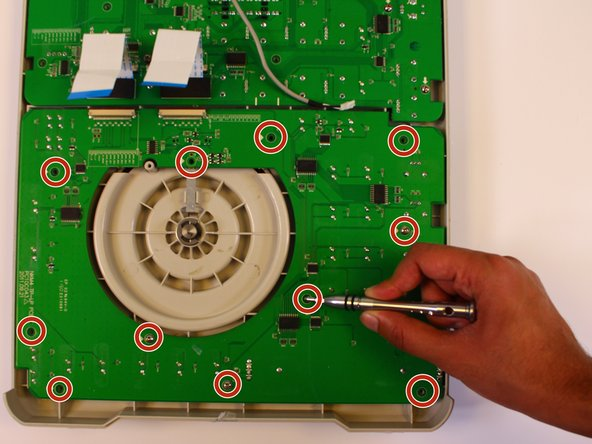 Loosen and remove the 11 12mm screws from the circuit board using a Phillips #2 screwdriver.