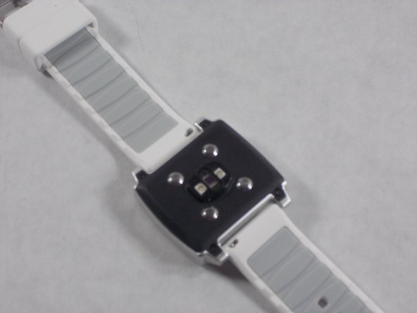 Flip the watch over and orient it such that the buckle is away from you and the back panel is revealed.