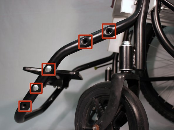 Make sure the two bolt holes on the footrest bar line up with two of the holes on the front frame
