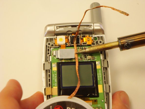 Place a piece of solder wick on top of the solder.