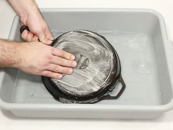 Thoroughly rinse the pan or skillet, then scrub it with steel wool and dish soap.