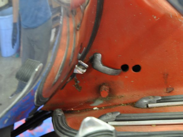 Using your hand, pull the engine cover retaining latch away from the scooter frame, then twist the latch clockwise to release the engine cover.