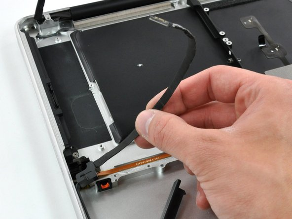 Image 2/2: Peel the hard drive cable from the adhesive securing it to the upper case, and maneuver the plastic retaining block out of the upper case.