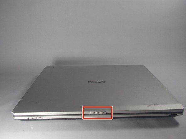 Flip the laptop over so that the front tab of the laptop faces you.
