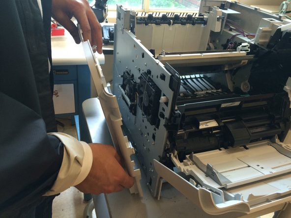 Start by loosening back side from clips, working your way to the front. Be careful when removing the panel clip near the front printer door (slide panel carefully past door).