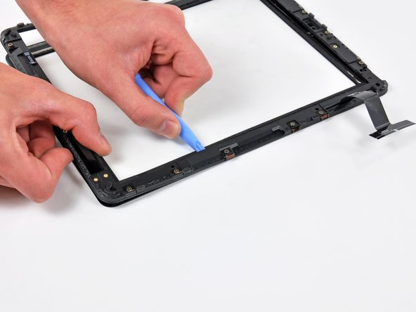 Carefully separate the lower edge of the ribbon cable side of the frame until you reach another area where rubber connects the frame to the glass panel.