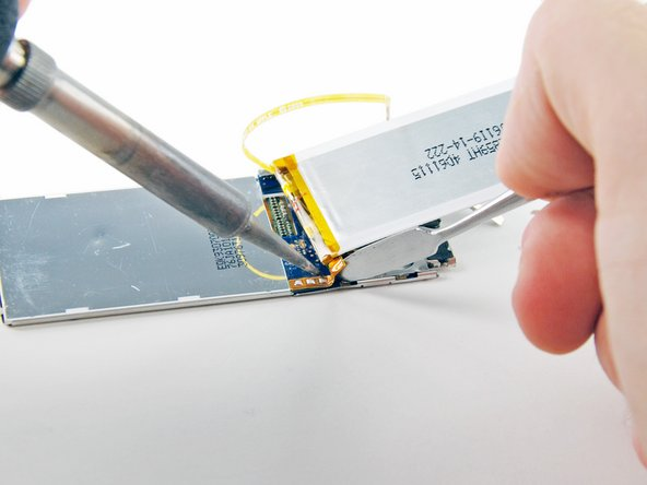 Image 1/1: The battery on the Nano is attached via solder pads with small holes that go through the battery ribbon cable and attach to flat pads on the face of the logic board. In this step, you will heat each solder pad individually while using a metal spudger to pry it up from the logic board.