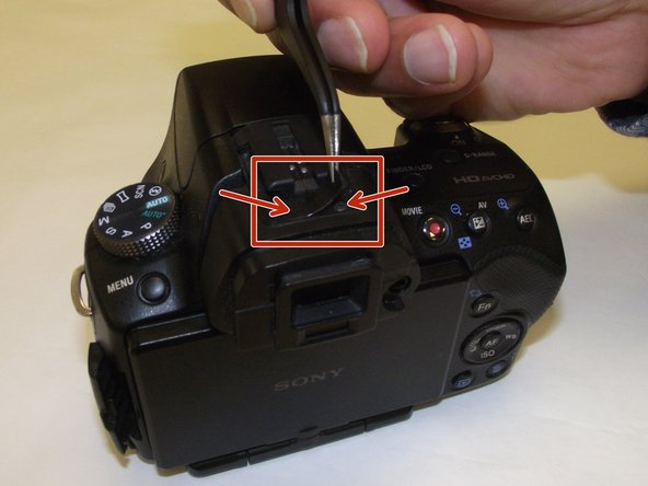 On the top of the camera there is a black plastic sticker that hides two screws which must be removed.