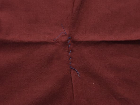 Continue sewing until you are past the rip. Knot and cut the excess thread.