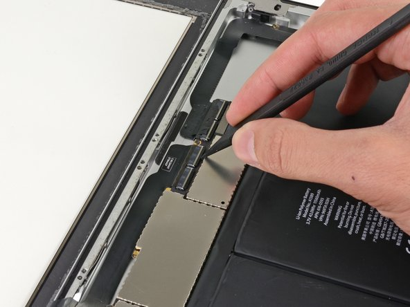 Image 1/3: If necessary, peel back the piece of tape that secures the digitizer ribbon cable to the logic board.