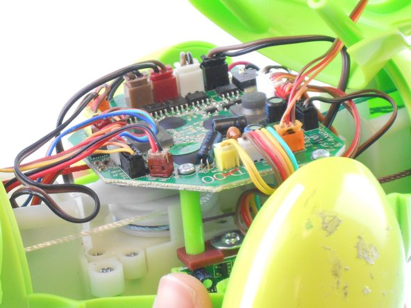 Disconnect the wire that connects the back cover of the dino to the main circuit board by carefully pulling on the orange wire connector with tweezers.