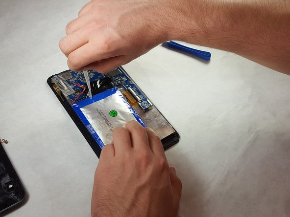 Remove the three pieces of adhesive placed over the edges of the battery.