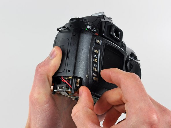 Image 1/2: Carefully pull the sides of the rear cover away from the body of the D70.
