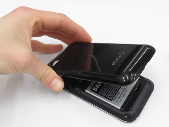 Pop the back case off by inserting your finger and pulling the case away from the phone.
