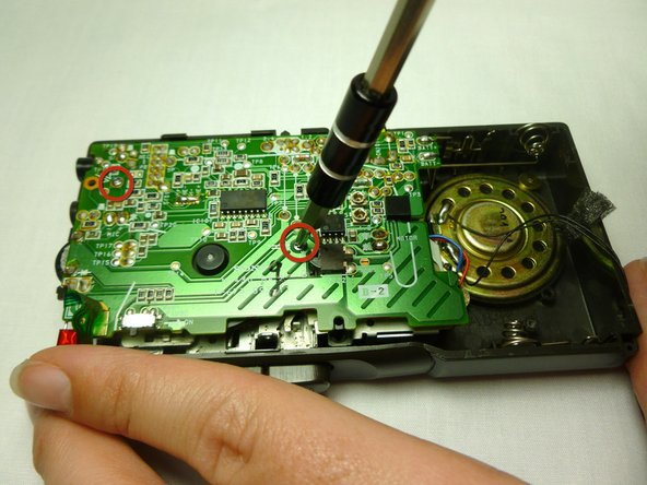 Using a #00 Phillips screwdriver, remove the two 1.4x3 mm screws securing the motherboard.
