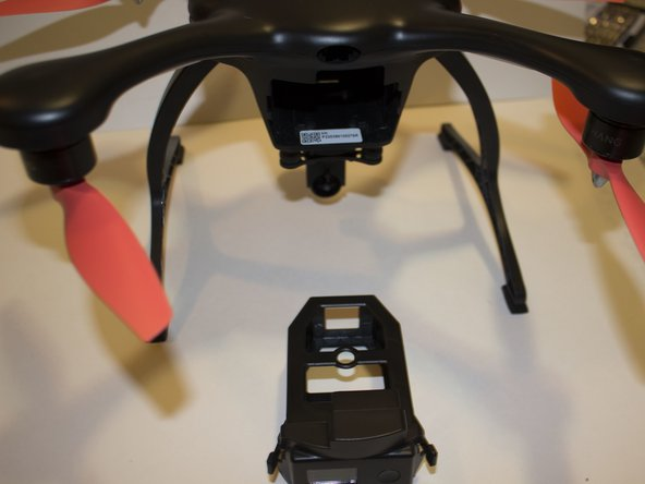 While the drone is facing forward, pinch the two tabs on the capsule, and pull it forward.