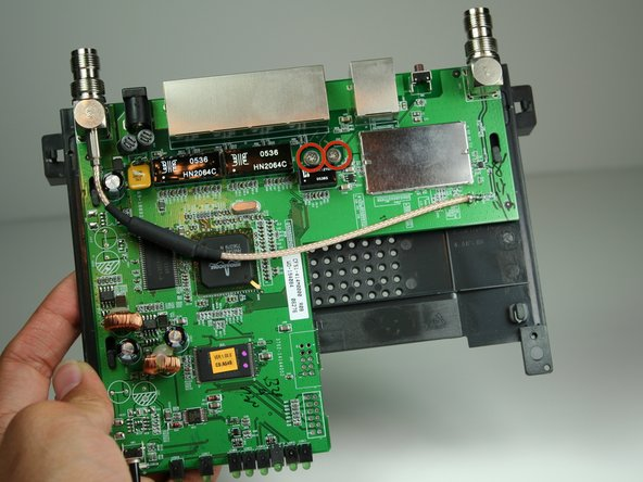 Image 1/2: Remove the two screws from the motherboard as indicated with the Phillips head screwdriver.