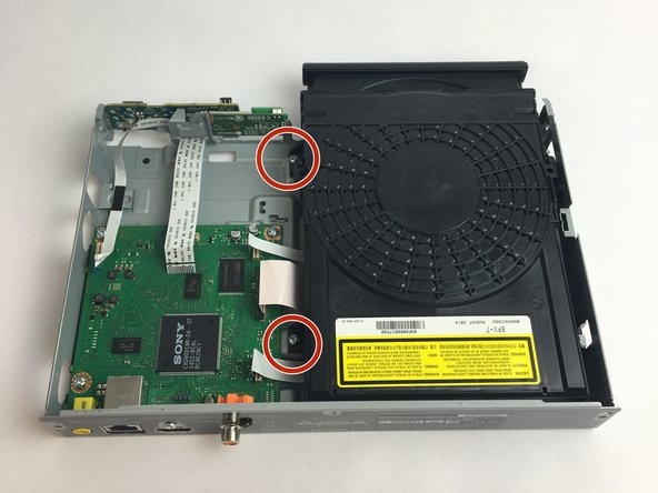 Remove the two screws that attach the disk drive to the frame using a #1 Phillips screwdriver.