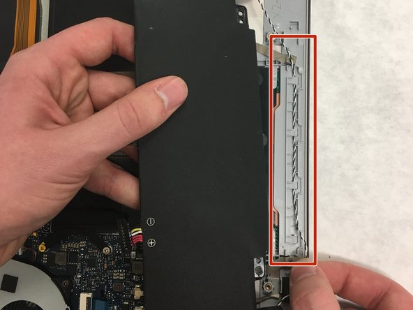 Carefully remove the speaker wires that are tucked underneath the tabs located at the edge of the laptop case.