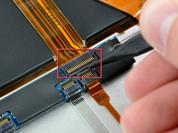 Use the pointed end of a spudger to flip up the retaining flap on the trackpad control cable socket.