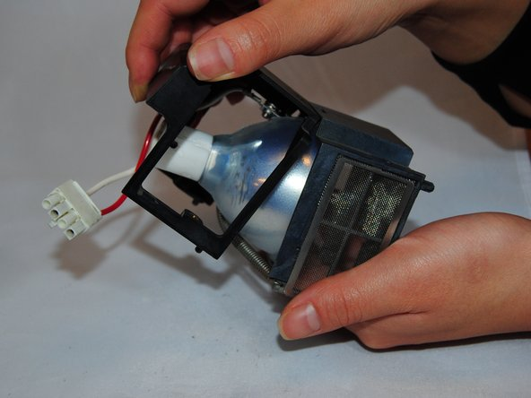 Lift up the middle of the bulb housing to remove it.