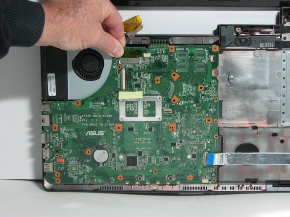 Image 1/3: The fan and several ports will be attached to the motherboard when it has been detached from the laptop.