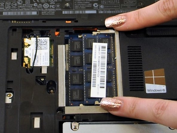 Press down and away from the ram cards on the tabs surrounding the ram cards.