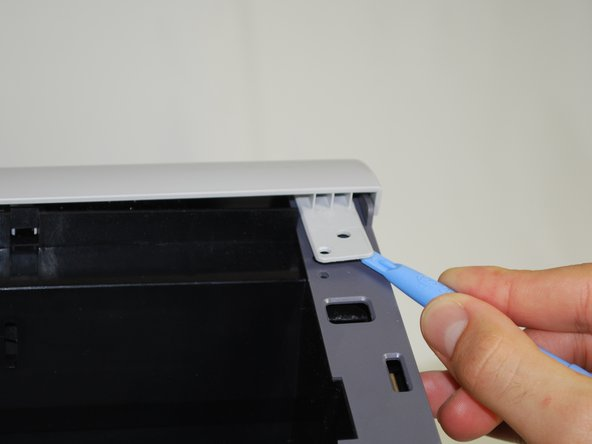 Using a plastic opening tool, gently lift one side of the top panel from its peg.