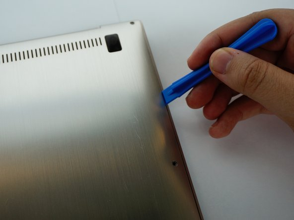 Using your iFixit Opening Tool, carefully slide it between the back panel.